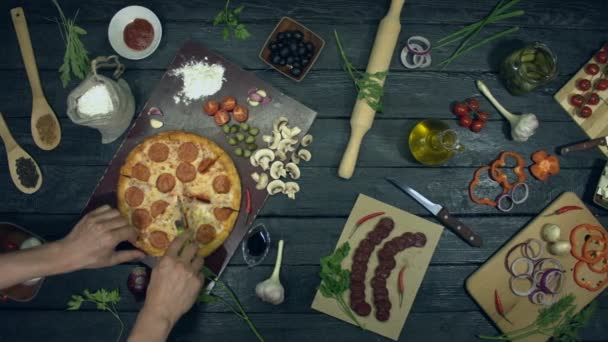 Pepperoni pizza on ecological black background.Man cuts a piece of pepperoni pizza and takes to him. Pizza with filling: salami, different cheese. There are also many other products on table for cooking and eating pizza.