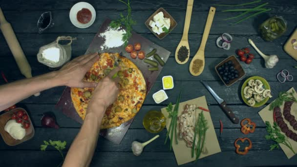 Cheeseburger pizza on ecological black background.Man cuts pizza on slices then two hands take two slices and sauces from table. Pizza consists of ingredients: cucumbers, spices, tomatoes, meat, chicken, sauce, cheese.