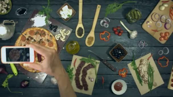 Pizza na ekologickém černém pozadí. Člověk si na stole vezme fotku telefonicky s pizzou. Masová Pizza s odlišným plněním: salám, houby, klobása, sýr, olivy. Na stole je také mnoho dalších produktů pro vaření a stravování pizzy.