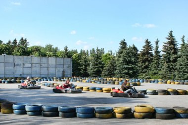 Odessa, Ukraine, 23.05.2006 Men go karting, in the open air. The track is made of old tires. In the background are green trees.