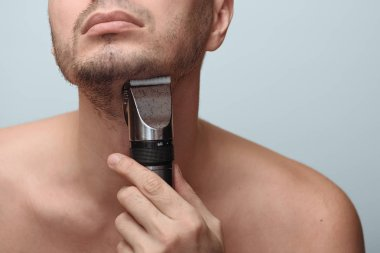 Cropped image of a young bearded man using electric shaver isolated over gray background