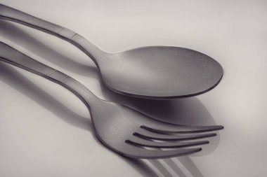 Fork and spoon with shadow on grey background.