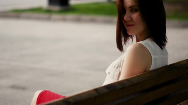 Beautiful young woman smiles mysteriously, sitting on a bench in a summer park. Portrait of a woman outdoors.