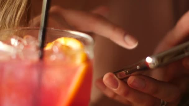 A beautiful woman with a smartphone in her hand drinks a cocktail at the bar