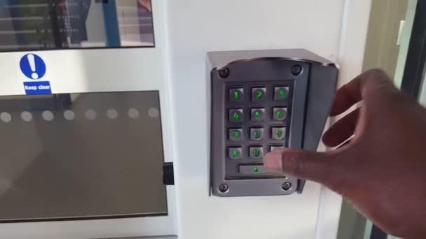 Etnická osoba zadávající bezpečnostní kód do vstupní klávesnice