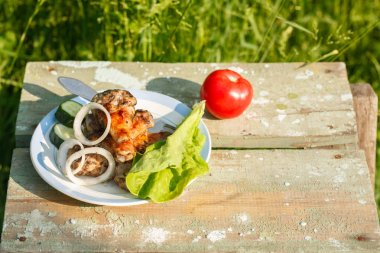 grilled chicken legs with fresh vegetables. Picnic in garden. On greenery background.