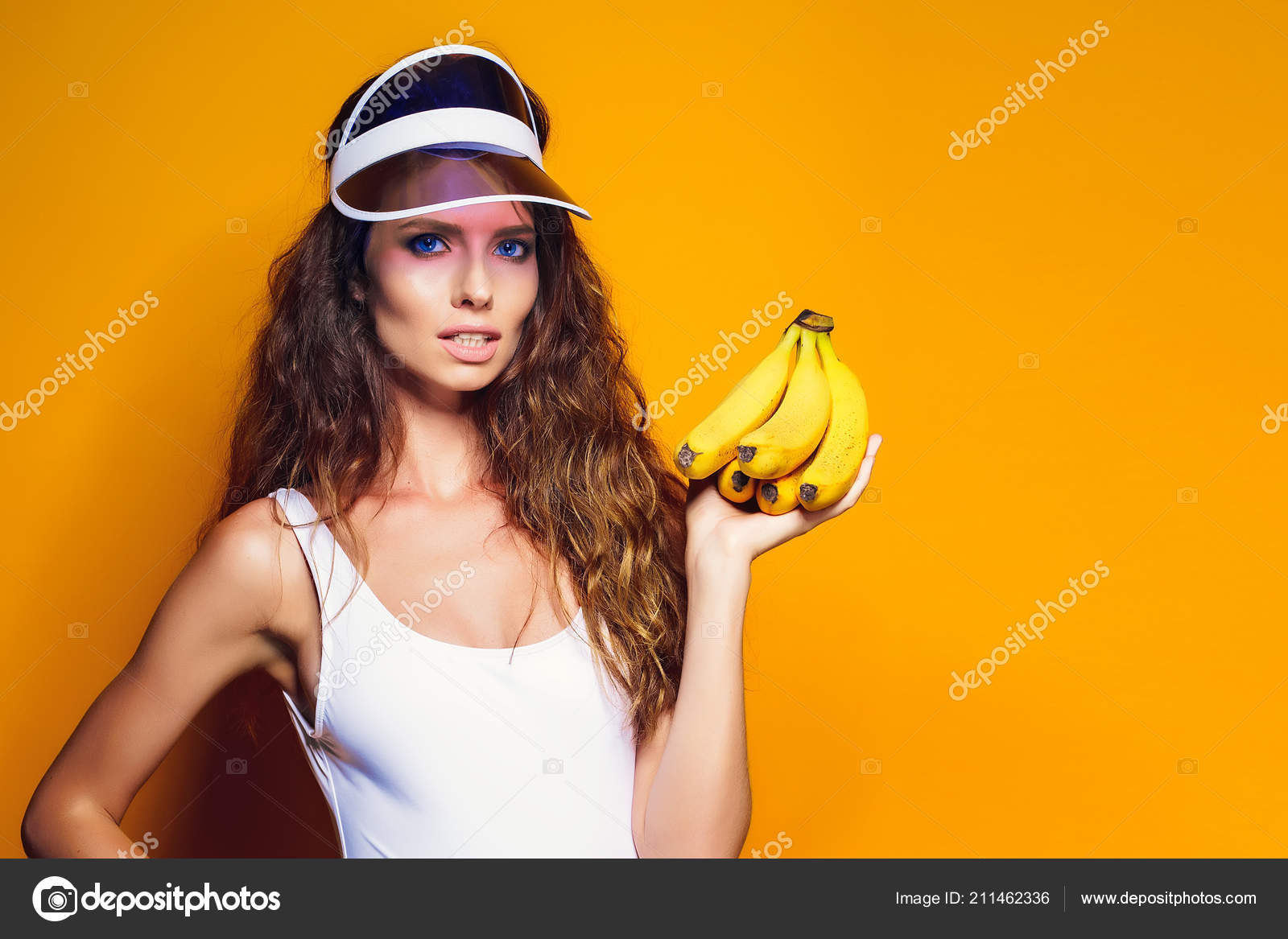 e6f5bd7cc21b8 Woman in swimsuit and blue shorts holding banana and posing isolated over  yellow background — Stock
