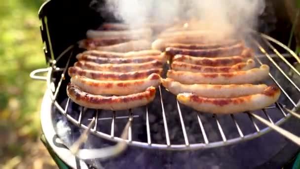 Grilovaná klobása na piknikovém hořícím grilu