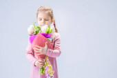 krásná holčička s kyticí bílých tulipánů