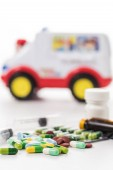 Medicine and toy ambulance on a white background