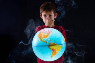 child covers his nose before the emissions of a globe