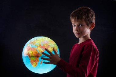 boy with a terrestrial globe looking at camera