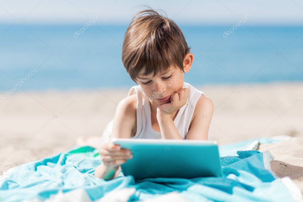 Boy with tablet lying on the beach a sunny day