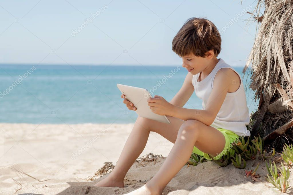 Child looks at tablet in the shade of a palm tree on the beach