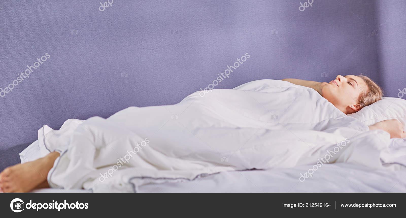 Mooi meisje slaapt in de slaapkamer liggend op bed u stockfoto