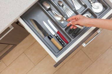 High angle top view cropped photo of woman hand open kitchen drawer by modern door handle, with different cutlery and take spoon to make dish, meal, food, eat