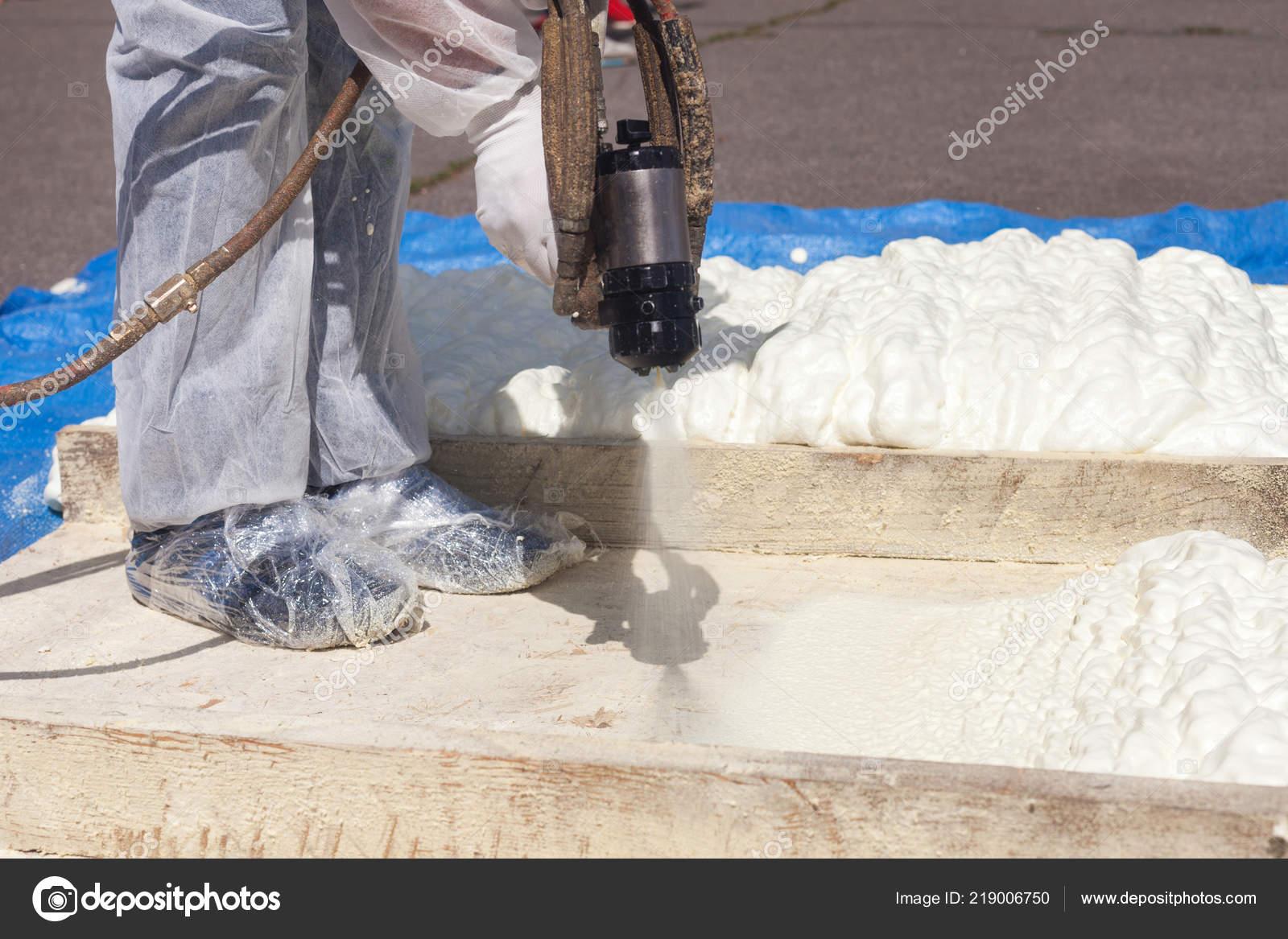 Technician Dressed Protective White Uniform Spraying Foam