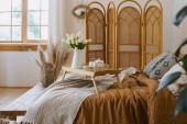 Tulipánok és reggeli tálca az ágyon teáskanállal és bögrével. Kényelmes apartman, bohém stílusú belsővel, hygge hálószobával, fapados üléssel, bambusz öltözőképernyővel, házi dekorációval, száraz növényekkel vázában