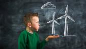 Kind bläst Kreidezeichnung einer Windkraftanlage auf Tafel-Konzept für alternative erneuerbare Energien und Umweltbildung.