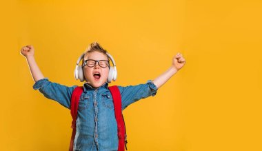 Cute little boy listening to music on headphones. School kid in glasses with bag.