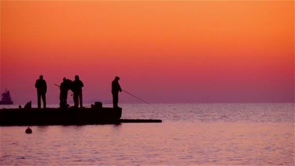 Rybáři loví ryby při východu slunce