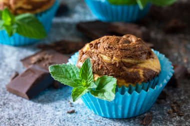 Muffins with chocolate and mint on the background of dark slate.