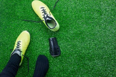 Table top view aerial image of sign of soccer or football season background.Flat lay accessories clothing man wear shoe on the artificial green grass wallpaper.Free space for design text and content.