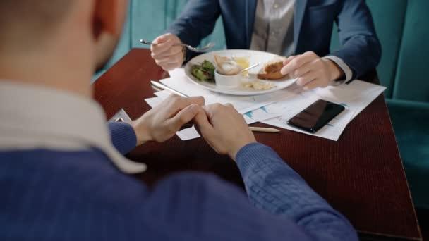 Dva mladí podnikatelé jsou mluvit, jíst potraviny, sedící naproti u stolu v restauraci