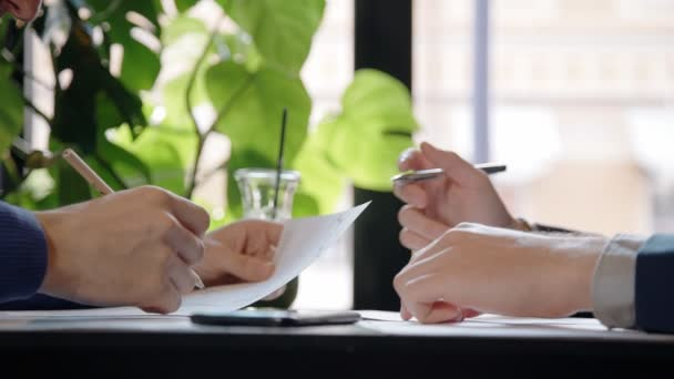 Close up of hands of two businessmen working on reports in the cafe.