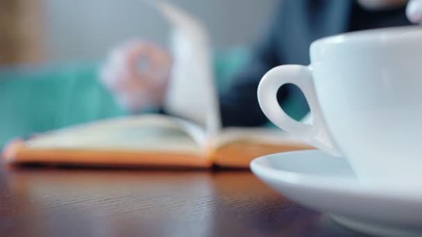 Zblízka šálek kávy na stole café s osobou stránkama, knihy na pozadí