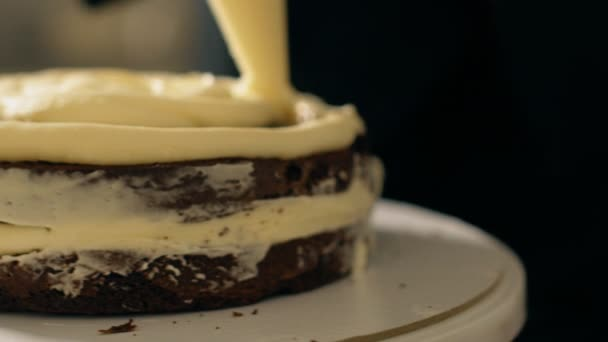 Close up of white cream is being put to the chocolate cake by confectioner.