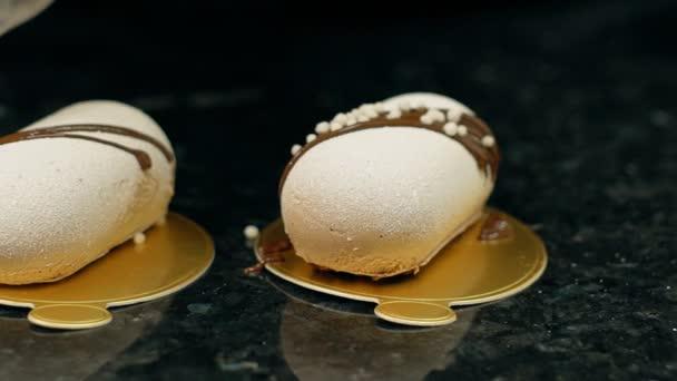 Detailní záběr z bílého pečiva na zlatých talířích zdobí cukrárnu s čokoládou a ořechy.