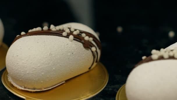 Detailní záběr z bílého pečiva, ležící v řadě a jsou zdobené čokoládou.
