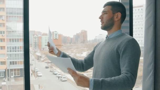 Mladý podnikatel hledá projekt při spuštění, stojící u okna v společnosti.