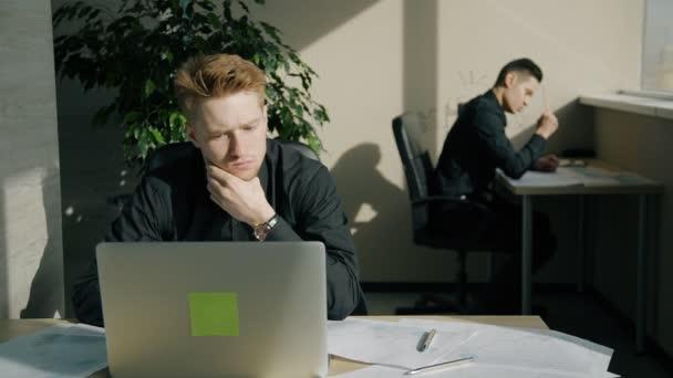 Mladý muž, pracující u stolu s notebookem, kolega psaní v moderní kanceláři