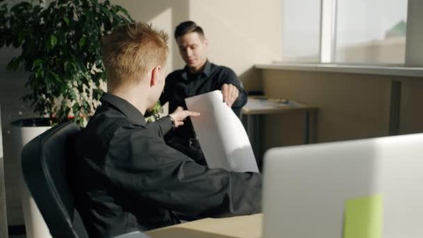 Mladí muži pracující na projektu, spolupracující v moderní kanceláři