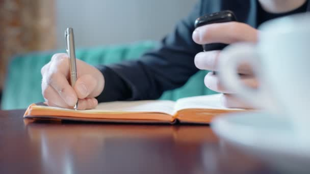 Close up of male hands taking notes in notebook and holding phone.