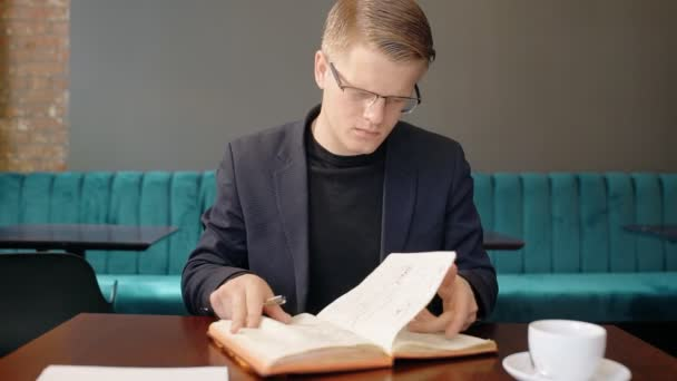 Portrait of businessman turning over the pages of his notebook in cafe.