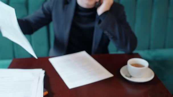 Mladý podnikatel pracuje na projektu, mluví o telefonu v kavárně interiéru.