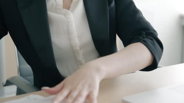 Sekretářka, práce s dokumenty v pracovišti s notebookem v moderní kanceláři