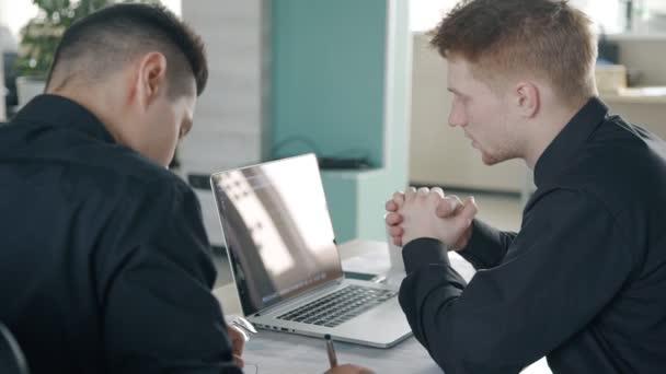 Két fiatal férfi projekten dolgozik együtt a modern iroda, látszó-hoz laptop.