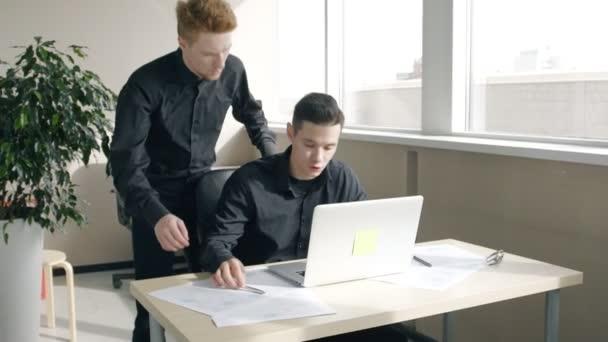 Giovani uomini daffari uomini discutendo di affari al tavolo con il computer portatile in ufficio moderno.