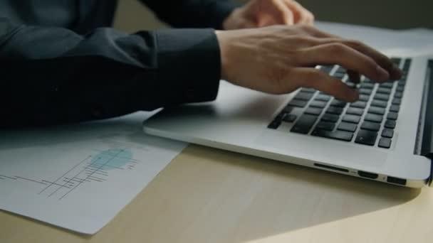 Muž zaměstnanec psát v pracovním procesu u stolu s notebookem uvnitř úřadu