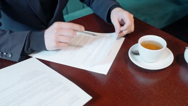 Hands of businessman reading contract in the cafe.