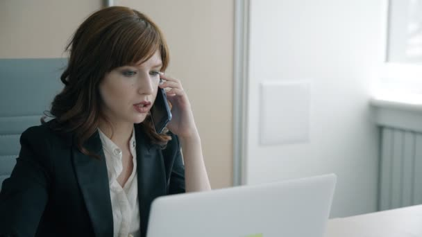Portrait of young businesswoman talking on phone in her private office.