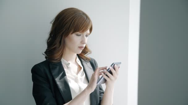 Young attractive business woman is using smartphone standing in bright office.