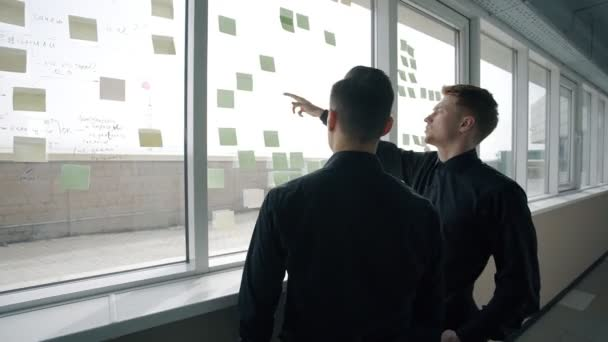 Young men are talking, pointing on notes on window in modern office.