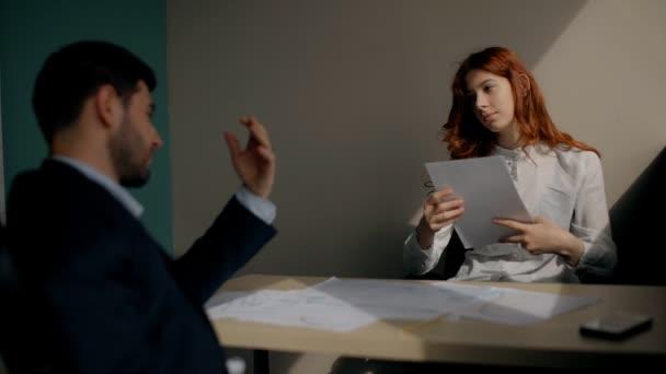 Mladí podnikatelé jsou diskuse o podnikání, sedící u stolu na pracovišti ve firmě