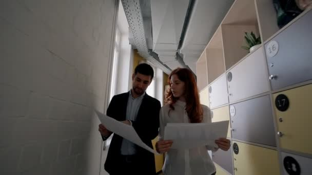 Young businessman and woman are talking about project, walking in large company.