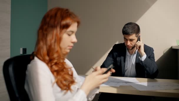 Young businessman talking on phone, female colleague using smartphone sitting in workspace.